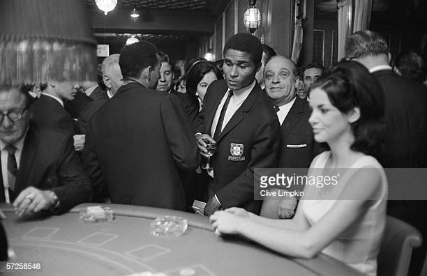 Portuguese striker Eusebio looks over at a game of blackjack in a sporting club in Kensington after the 1966 World Cup in England 1st August 1966