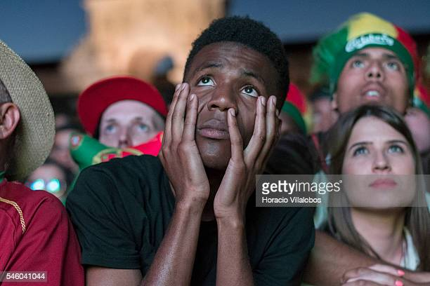 Portuguese supporters react during the match while watching their national team play against France for the final of UEFA Euro 2016 on a giant screen...