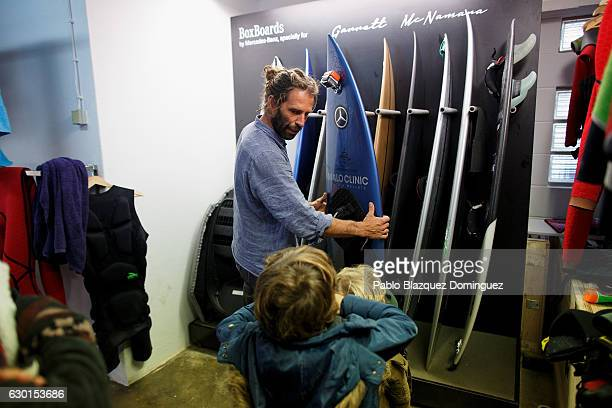 Portuguese surfer Hugo Vau shows his boards to some children at his warehouse after a big waves session on December 17 2016 in Nazare Portugal...