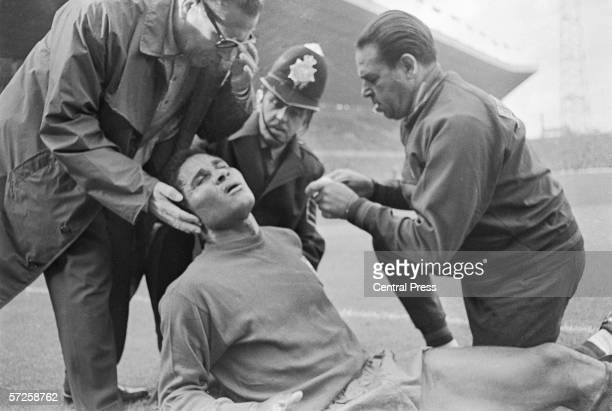 Portuguese team doctor Dr Jao Da Silver Rocha left tending to the team's star striker Eusebio at Old Trafford after a clash in the Portugal vs...
