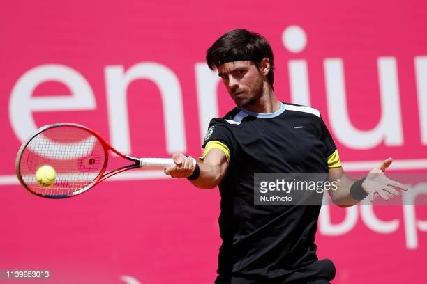 Portuguese tennis player Gastao Elias returns the ball to Australian player Alexei Popyrin during their Millennium Estoril Open ATP Singles...