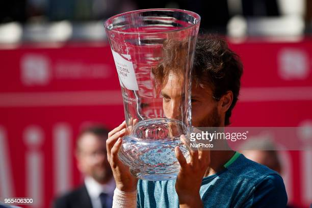 Portuguese tennis player Joao Sousa kisses his trophy during the award ceremony after winning the Millennium Estoril Open ATP Singles tournament in...