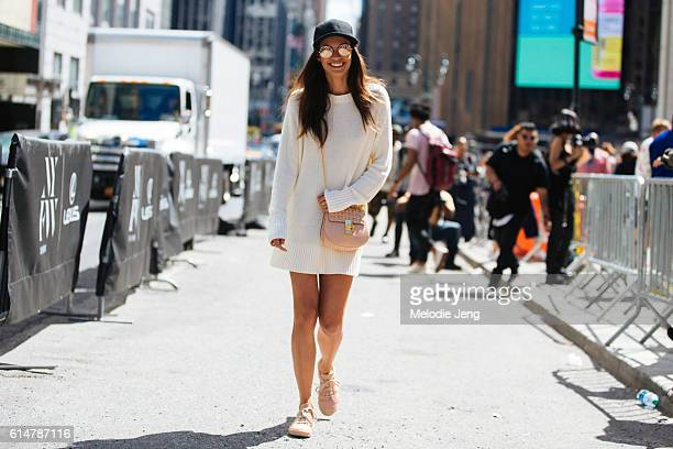 Portuguese Victoria's Secret Angel model Sara Sampaio wears circular reflective sunglasses a white sweater knit dress a pink Chloe purse and pink...