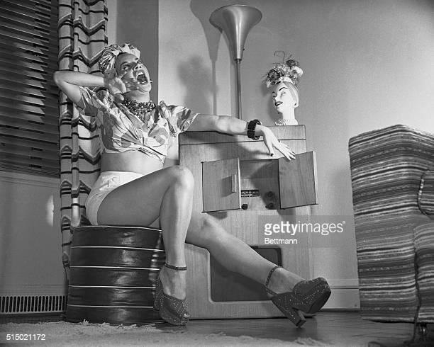 Carmen Miranda Sitting on Ottoman Singing
