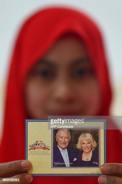A Pos Malaysia postal services employee poses with a special commemorative stamp to mark Britain's Prince Charles Prince of Wales and Camilla Duchess...