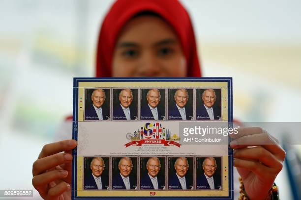 A Pos Malaysia postal services employee poses with special commemorative stamps to mark Britain's Prince Charles Prince of Wales and Camilla Duchess...