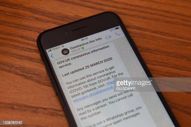 Posed picture taken in Marsden on March 25, 2020 shows a communication from the British government's Coronavirus Information Service on WhatsApp...