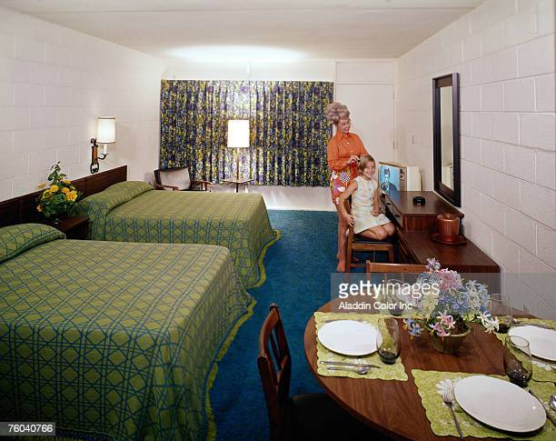Posed portrait of a girl who kneels on a chair as a her mother combs her hair in a room at the Vancouver Motel Myrtle Beach South Carolina 1960s