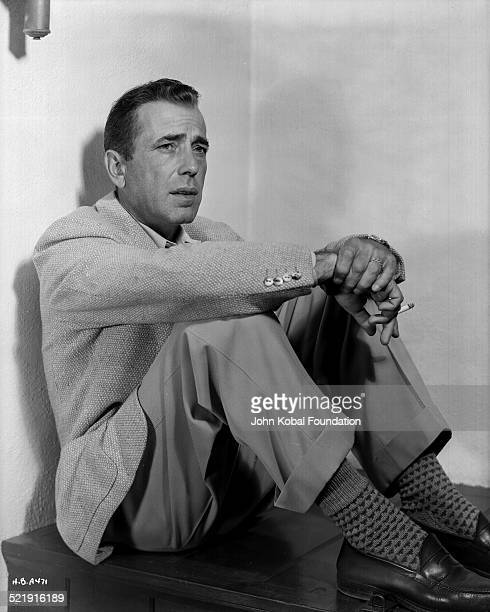Posed portrait of actor Humphrey Bogart sitting against a wall and smoking a cigarette for Warner Bros Studios 1949