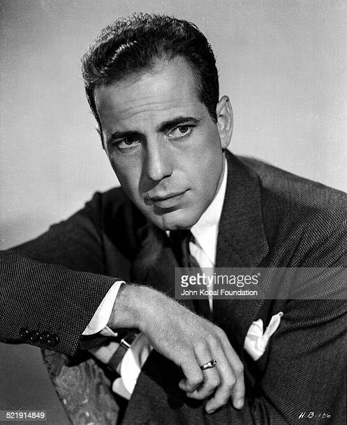Posed portrait of actor Humphrey Bogart wearing a black suit and tie for Warner Bros Studios 1938
