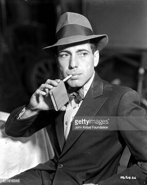 Posed portrait of actor Humphrey Bogart wearing a hat and bow tie with a pack of cigarettes, for Warner Bros Studios, 1938.