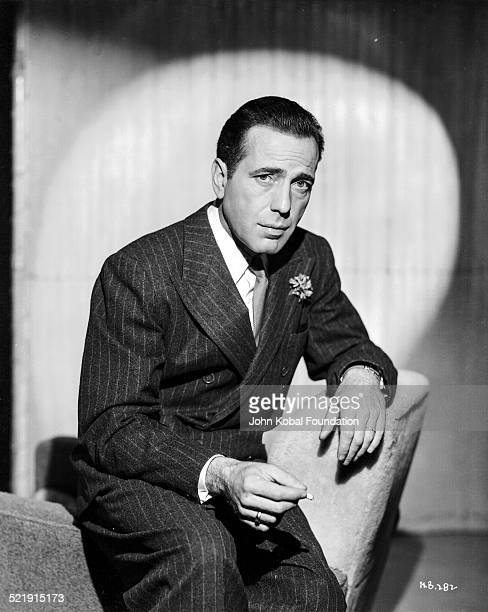 Posed portrait of actor Humphrey Bogart , wearing a suit and tie and smoking a cigarette, for Warner Bros Studios, 1946.