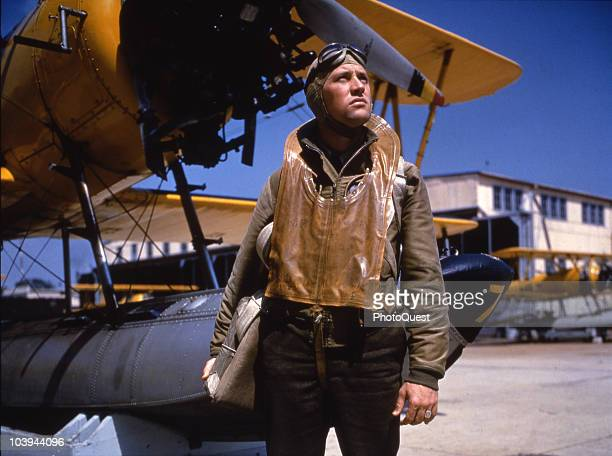 Posed portrait of an unidentified US Navy pilot as he poses in front of an N3N-1 training plane parked on the tarmac at Naval Air Station Pensacola,...