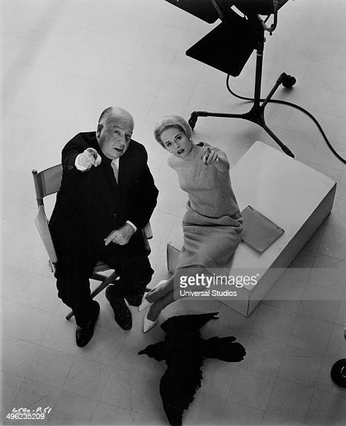 Posed portrait of director Alfred Hitchcock and actress Tippi Hedren pointing up towards the camera on the set of the movie 'The Birds' 1963