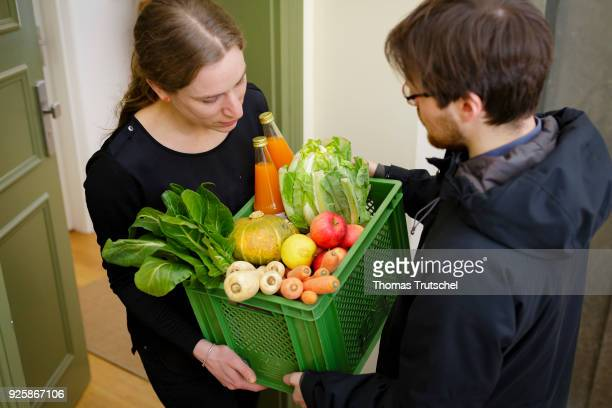 Posed Scene A vegetable box scheme with fresh organic fruit and vegetables is handed over at the front door by a supplier to a consumer on March 01...