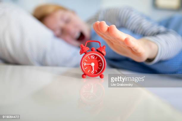 Posed Scene An alarm clock stands on a bedside table while a woman is sleeping in bed on February 13 2018 in Bonn Germany
