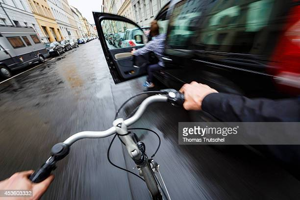 Posed scene of a cyclist evading on the street because a driver is suddenly opening the door of a car on August 04 in Berlin Germany