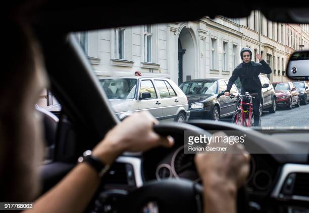 Posed scene of a cyclist gets excited about a car driver on February 13 2018 in Berlin Germany