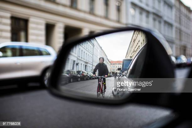 Posed scene of a cyclist seen through the side mirror of a car on February 13 2018 in Berlin Germany