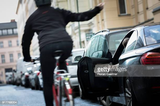 Posed scene of a driver who suddenly opens the door of the car during a cyclist passes the car on February 13 2018 in Berlin Germany