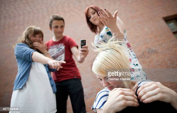 Posed scene of a girl being bullied by classmates classmates are hitting her and are video recording on May 31 in Berlin Germany