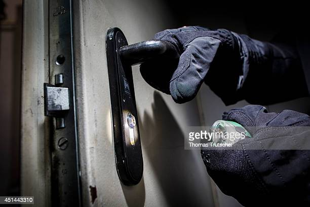 Posed scene of a man opening a door with gloves and flashlight on June 27 in Berlin Germany The photo symbolizes the increasing risk of burglary in...