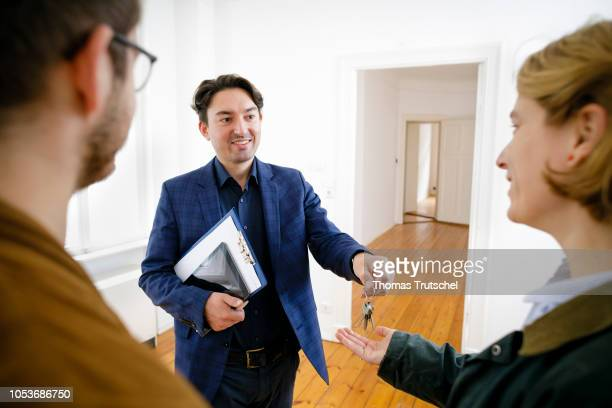 Posed scene on the topic of property market A estate agent hands flat keys to a young couple on October 25 2018 in Berlin Germany