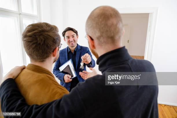 Posed scene on the topic of property market A estate agent hands flat keys to a gay couple on October 25 2018 in Berlin Germany