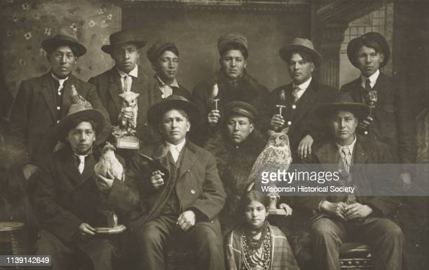 Posed studio group portrait in front of a painted backdrop of Winnebago Indian men and one young woman Black River Falls Wisconsin 1910 Each of the...