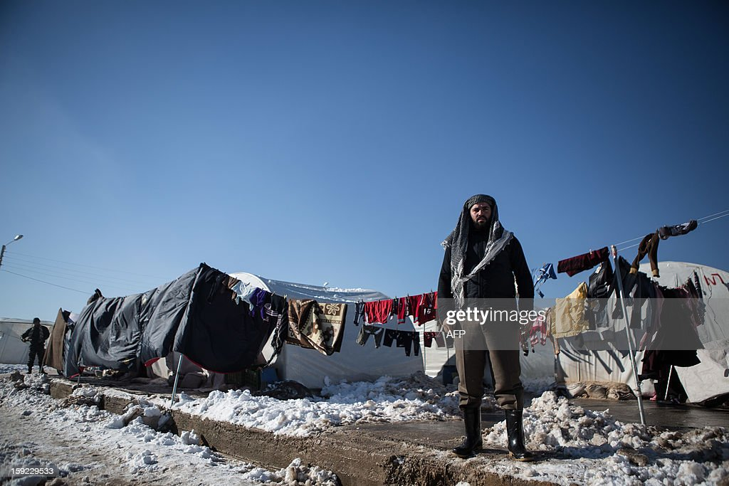 A poses in front of clothes drying on a line in a Syrian refugees camp in Azaz, near the Turkish border, on January 10, 2013 after snow falls. Snow carpeted Syria's war-torn cities but sparked no let-up in the fighting, instead heaping fresh misery on a civilian population already enduring a chronic shortage of heating fuel and daily power cuts.