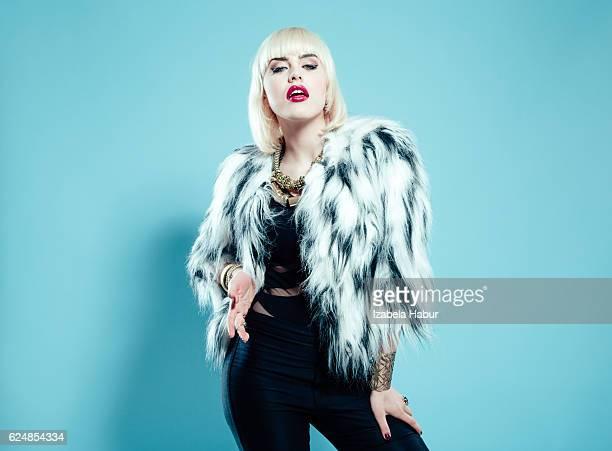 Posh blonde woman wearing fur jacket and gold jewlery