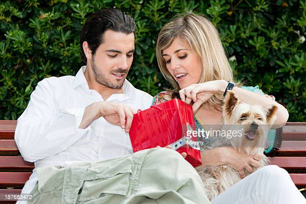 Posh couple sitting on park bench relaxing after shopping