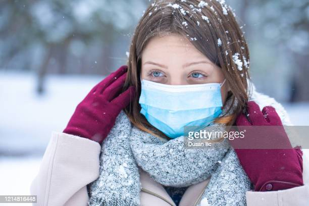 posing on the snow with protective mask - coronavirus winter stock pictures, royalty-free photos & images