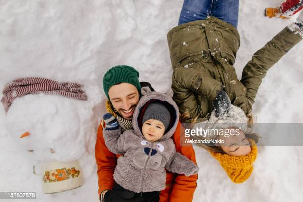 posing with our snowman - christmas family stock pictures, royalty-free photos & images