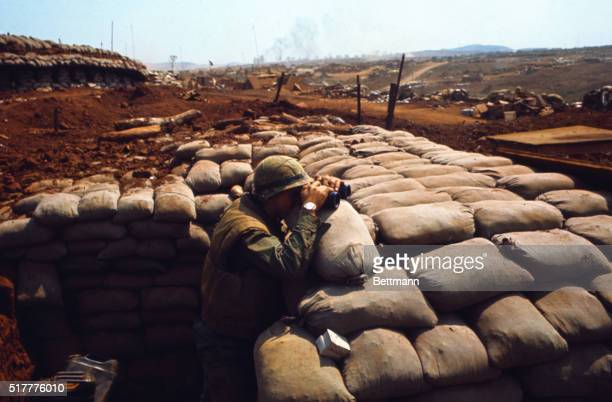 Positioned in a sand bagged bunker a US Marine checks position of communist forces with binoculars