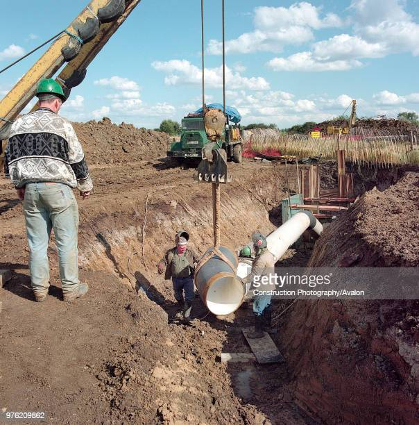 Positioning bend section of gas supply pipe in trench on the Essex marshes for the Barking Reach Power Station the largest of the 1990s Dash For Gas...