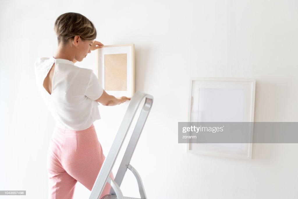 Positioning paintings next to each other on the wall : Stock Photo