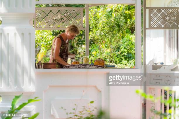 mujer madura positiva de 55 años que sirve una mesa para el desayuno con comida vegetariana fresca. la vista desde el exterior a través de una ventana. - 50-59 years and women only fotografías e imágenes de stock