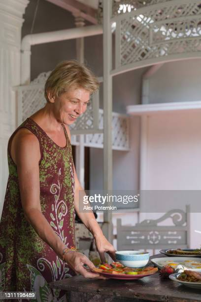 positive 55-years-old mature woman serving a table for breakfast with fresh vegetarian food. - 55 59 years stock pictures, royalty-free photos & images