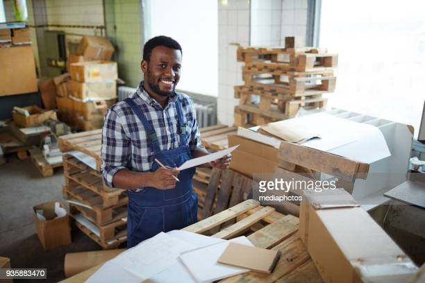 Positive African manual worker examining sketches