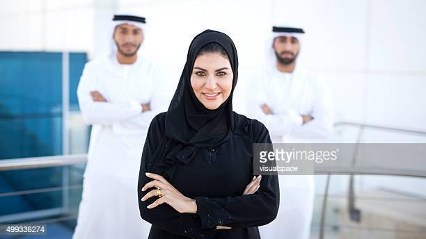 positive arab female enterpreneur with two men in background - perzische golfstaten stockfoto's en -beelden