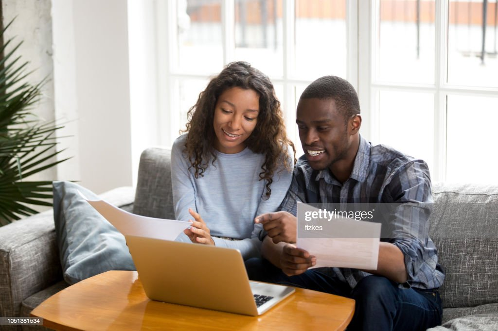 Positive black couple with bills and laptop at home : Stock Photo