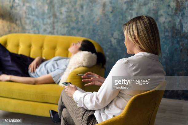 positive blonde middle-aged woman psychologist talking to girl patient - psychiatrist's couch stock pictures, royalty-free photos & images