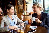 positive young female managers drinking tea