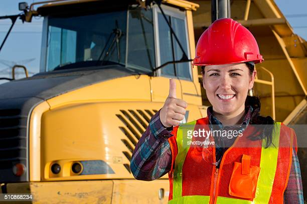 Positive Female Construction Worker and Heavy Hauling Truck