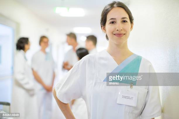 positive female nurse in nursing home - infermiera foto e immagini stock