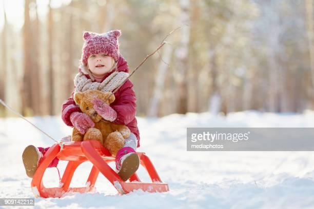 Positive Mädchen reiten mit Spielzeug Bär auf Schlitten