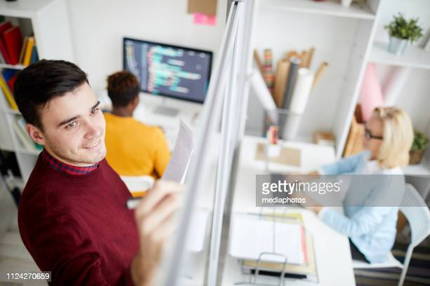 Positive handsome young creative man holding papers and writing on glassy board while elaborating strategy