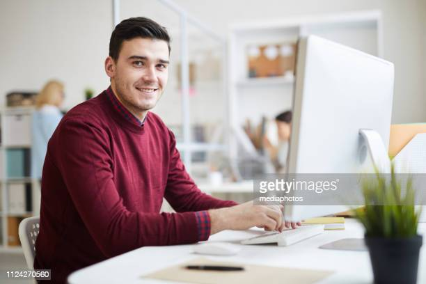 positive handsome young graphic designer in red sweater sitting at desk and using modern computer while looking at camera in office of programming company - red shirt stock pictures, royalty-free photos & images