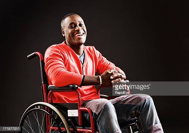 Positive Mann im Rollstuhl lacht in sein Schicksal
